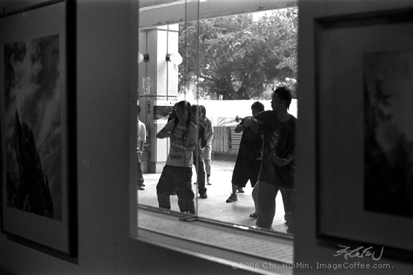 Practice makes perfect: <br/>Those young students were dancing outside a gallery. They used the glass as the mirror in order to look themselves.